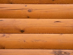 Wooden painted wall with raindrops. Wet surface. Logs, timber.