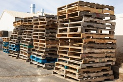 Wooden pallets stacked along a wall in a warehouse lot.  Stacks of pallets under a pale sky.  Loading dock with pallets piled high.