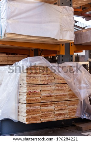 Wooden panels stored inside an industrial warehouse on metal shelving for use in construction and building, nobody in view