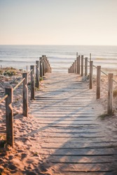 Wooden path on the beach during golden hour in Porto, Portugal