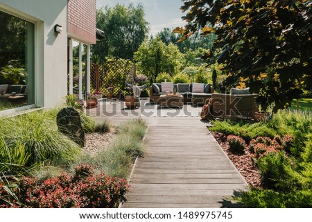 Wooden path to terrace in the garden with trendy garden furniture