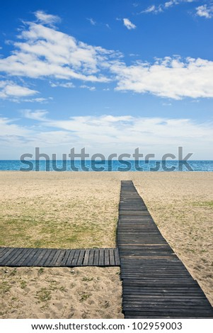 Wooden path to the sandy beach on Costa del Sol in Spain between Marbella and Puerto Banus.