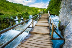 Wooden pathway climbing a raging raver in the Plitvice Lakes National Park in Croatia, shot using a slow shutter speed