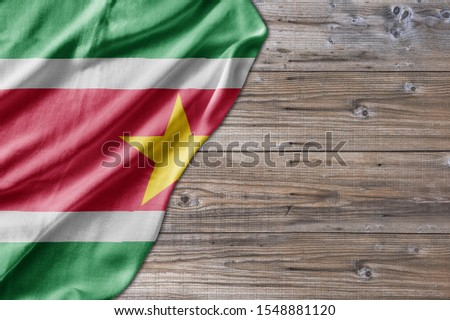 Wooden pattern old nature table board with Suriname flag #1548881120