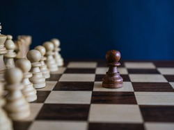 Wooden pawn alone against white set of pieces