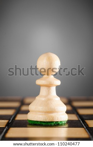 wooden pawn on gray background