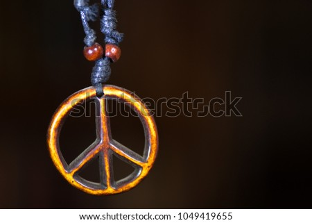 Wooden peace symbol attached to string necklace fairies love not war.