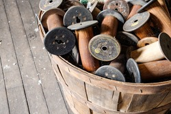 wooden peach basket full of old silk thread spools on an old factory floor