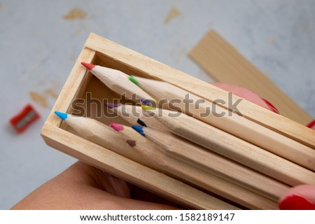 wooden pencil case with colour pencils on a creativ grey background for back to school #1582189147