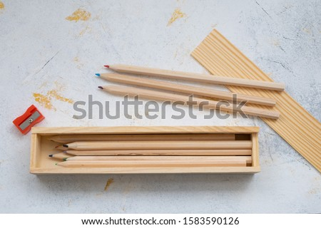 wooden pencil case with colour pencils on a creativ grey background for back to school #1583590126