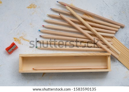 wooden pencil case with colour pencils on a creativ grey background for back to school #1583590135