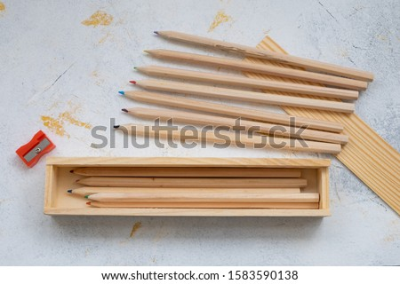 wooden pencil case with colour pencils on a creativ grey background for back to school #1583590138