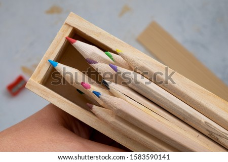 wooden pencil case with colour pencils on a creativ grey background for back to school #1583590141