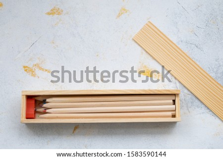 wooden pencil case with colour pencils on a creativ grey background for back to school #1583590144
