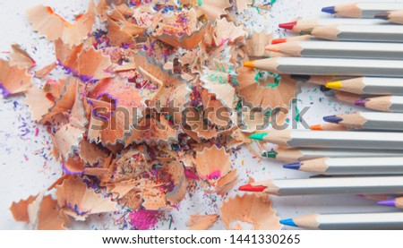 Wooden pencil shavings and colorful crumbs of graphite from sharpener. Abstract image: urgency and importance concept.