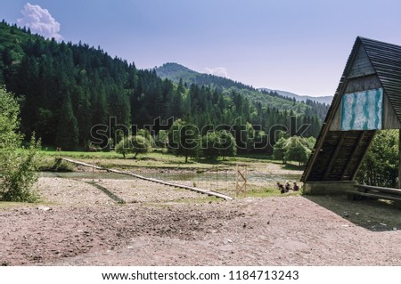 Wooden pendant bridge across the mountain river. Mountain river