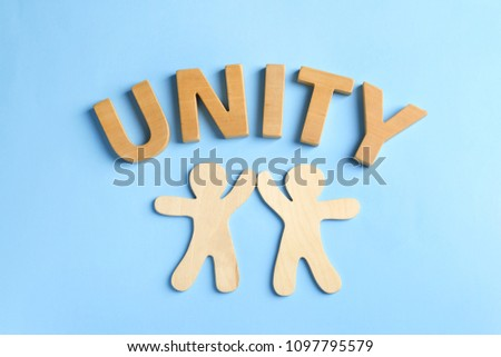 Wooden people giving high five and word UNITY on color background. Unity concept #1097795579