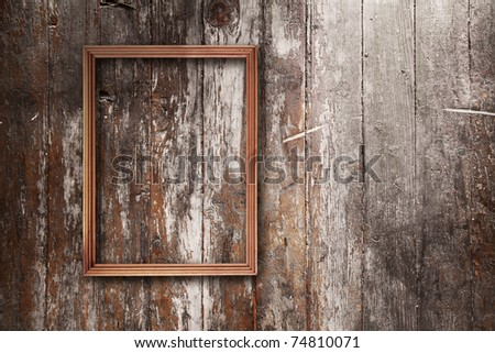 wooden photo frame on old wooden wall