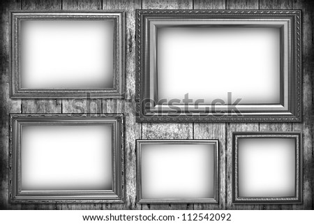 Wooden photo frame on old wooden wall in black and white.