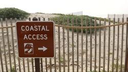Wooden picket fence, sandy misty beach, Encinitas California USA. Pacific ocean coast, dense fog on empty sea shore. Coastline near Los Angeles, grass in milky smog haze. Coastal access sign and arrow