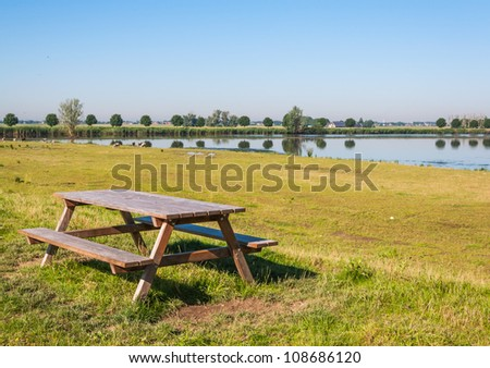 Wooden picnic table near a lake in a Dutch nature area.