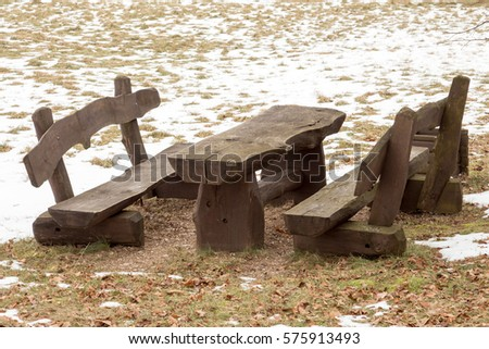 Wooden picnic table with benches in the winter park #575913493