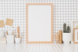Wooden picture frame mockup on a checkered wall, wooden supplies, boxes, brushes on home office desk.