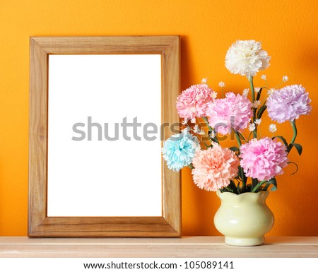 wooden picture frame on orange wall with flowers