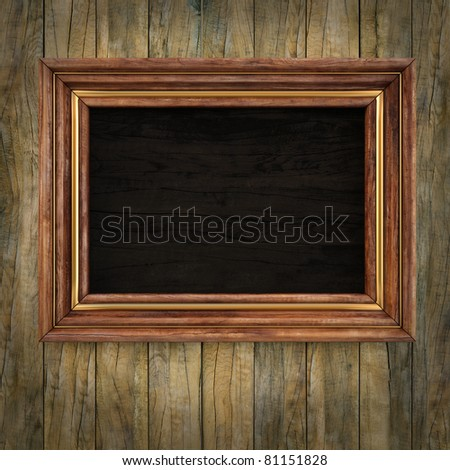 wooden picture frame on the old wooden wall. - stock photo