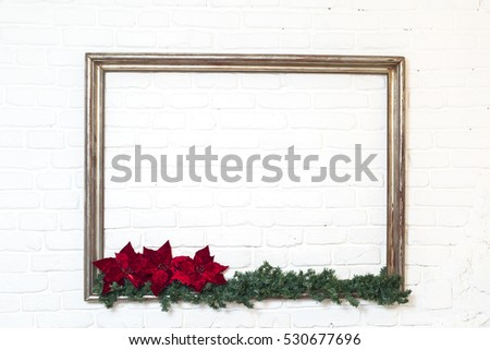 Wooden picture frame with a branch of pine-tree and red flower on a white brick background