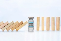 Wooden pieces domino effect stopping fall with a Covid-19 vial vaccine, next to stand wooden pieces  Concept: Covid-19 vaccine stopping crisis and risk, protection concept.