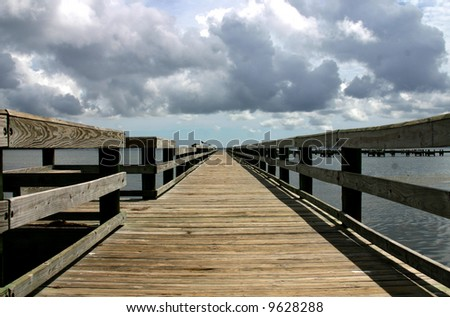 Wooden pier advancing into the darkening horizon