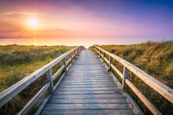 Wooden pier at sunset along the dune beach, North Sea, Germany