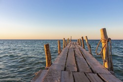 Wooden pier at the sunset. Evening sky over sea with footbridge. Calm evening landscape. Empty pier at seaside with copy scape. Pier in warm sunset light. Horizon over sea. Marine travel.