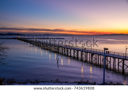 Wooden pier at White Rock, BC, Canada extends diagonally into image... its twinkling lights reflected in the sea.  The sun is setting with flaming reds and oranges over the Gulf and San Juan Islands  #743619808