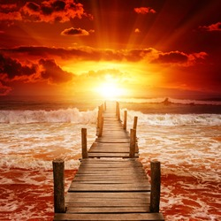 Wooden pier for boats in ocean on background epic sunset.