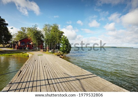 Wooden pier for yachts. Traditional house colored with falu red dye. Summer vacations, recreation, leisure activity, service, private vessels. Björkö island, lake Mälaren, Sweden Stock fotó ©