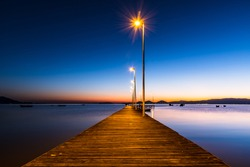 wooden pier in calm sea at sunrise, blue hour, fishing boats and land on the horizon, under a blu and golden sky