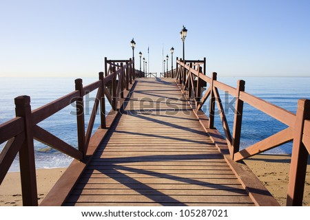 Wooden pier in good condition with barriers and lanterns on a calm Mediterranean Sea in Marbella, Costa del Sol, Andalusia, Spain.