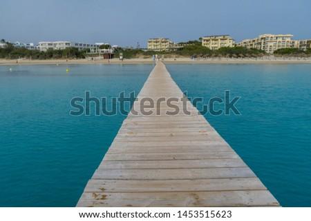 Wooden pier in the turquoise sea. Mallorca. Alcudia. Playa de Muro. #1453515623