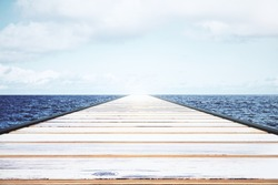 Wooden pier in the water with light sky