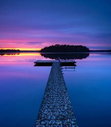 Wooden Pier into calm lake covered by fallen leaves  in autumn after sunset