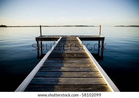 Wooden pier / jetty stretches out into an idyllic ocean