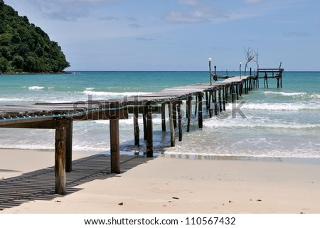 Wooden Pier Leading out to a Calm Blue Sea