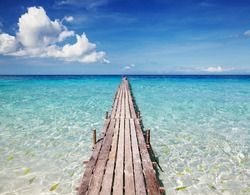 Wooden pier on a tropical island, clear sea and blue sky