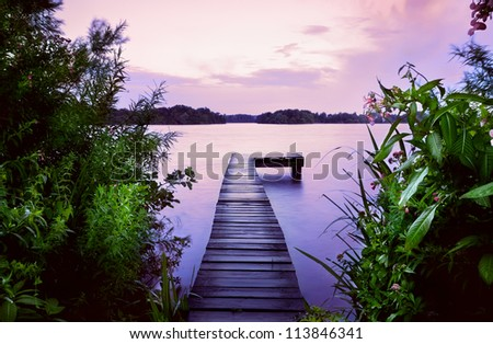 wooden pier on lake and summer flowers at sunrise