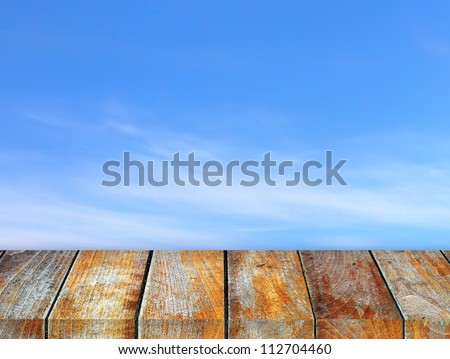 Wooden pier on sunny day with cloudy sky