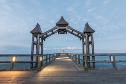 Wooden pier on the Baltic Sea. View to the horizon with sunset and clouds. Illuminated jetty with wooden arch and diving bell in the background on the island of Ruegen