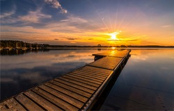 Wooden pier on the lake at sunset. Pier sunset. Sunset lake pier. Lake pier at sunset landscape