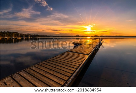 Wooden pier on the lake at sunset. Pier sunset. Sunset lake pier. Lake pier at sunset landscape Foto d'archivio ©